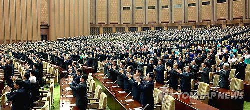 un monton de gente en la asamblea norcoreana de pie y aplaudiendo